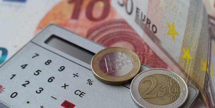 billets et pièces de monnaie autour d'une calculatrice